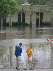 Onlookers view the rising floodwater surrounding the University of Iowa Museum of Art on Riverside Drive on June 15, 2008.