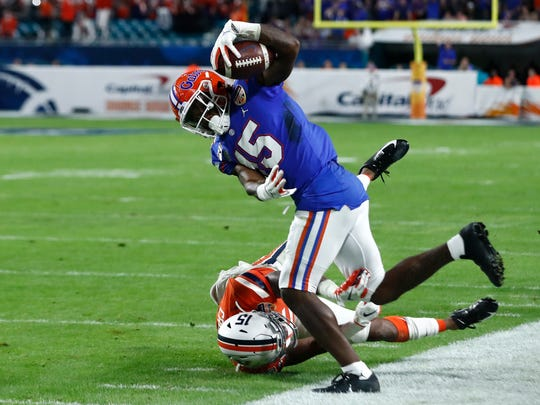 Florida wide receiver Jacob Copeland (15) makes a catch over Virginia safety De'Vante Cross, bottom, during the first half of the Orange Bowl NCAA college football game, Monday, Dec. 30, 2019, in Miami Gardens, Fla. (AP Photo/Brynn Anderson)