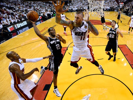 San Antonio Spurs forward Kawhi Leonard (2) goes to the basket as Miami Heat forward Chris Andersen (11) defends in the first half in Game 4 of the NBA basketball finals in Miami, Thursday, June 12, 2014. The Spurs won 107-86. (AP Photo/Larry W. Smith, Pool)