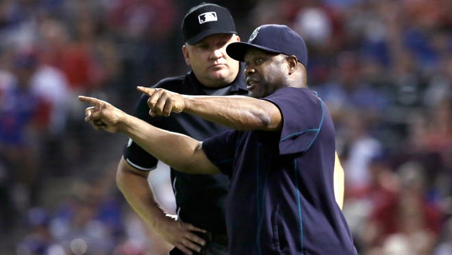 Seattle Mariners manager Lloyd McClendon, right, argues a call with umpire Jeff Nelson during the fourth inning of a baseball game against the Texas Rangers in Arlington, Texas, Friday, Sept. 18, 2015.