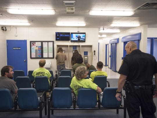 Recently arrested people wait to go through the booking process at Larimer County Jail Friday, September 30, 2016.