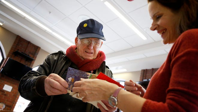 "Navy and Army veteran Dick Walters, of Bath, and Denise Kartzman, of Horseheads, smile as they look through a handful of holiday cards that are headed to military members in Kuwait Saturday at the Corning UPS store. The cards were collected through the 2016 Casimir ""Cas"" J. Krolak Holiday Card Drive."