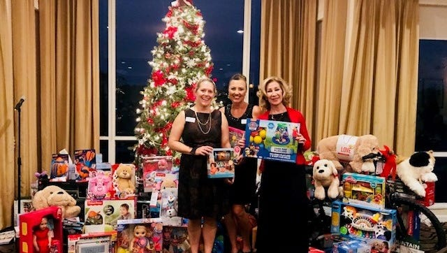 Santa's Elves co-chairs Ellen Houts and Heidi Monsour and volunteer Brenda Woolston were excited to receive lots of toys and gifts for the Hibiscus children at the Raymond James Annual Toy Drive Party.