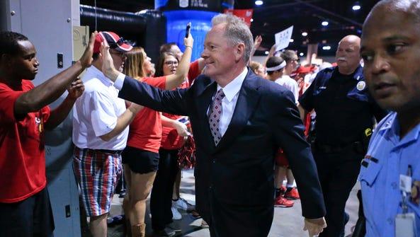 Louisville head coach Bobby Petrino greets fans he