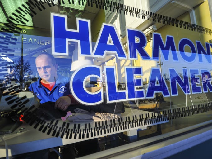 Joe Cruz, owner of Harmony Cleaners, sews a pair of