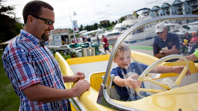 Kevin Walter and his son Luke, 5, of Charlotte, check out a 1958 Carr-Craft boat during the Blue Water Antique and Classic Boat Show at the River Street Marina in Port Huron.