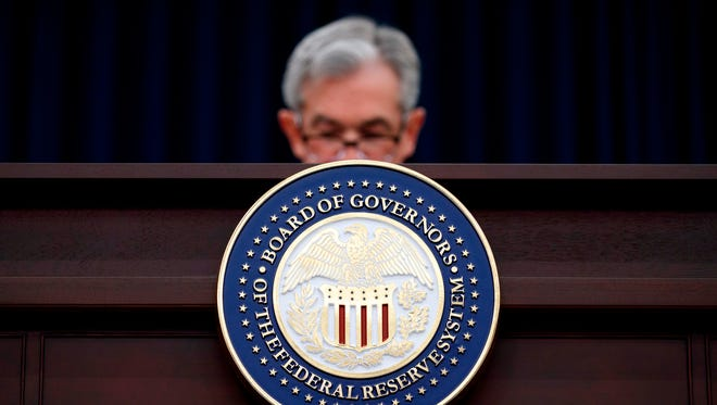 Federal Reserve Chairman Jerome Powell looks to his notes as he speaks during a news conference following the Federal Open Market Committee meeting in Washington.  As the government drives to loosen restraints on banks, the Federal Reserve is set to ease a rule aimed at defusing the kind of risk-taking on Wall Street that helped trigger the 2008 financial meltdown.