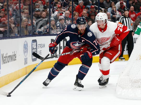 Columbus Blue Jackets' Nick Foligno, left, looks for an open pass as Detroit Red Wings' Gustav Lindstrom, of Sweden, defends during the second period of an NHL hockey game Friday, Feb. 7, 2020, in Columbus, Ohio. (AP Photo/Jay LaPrete)