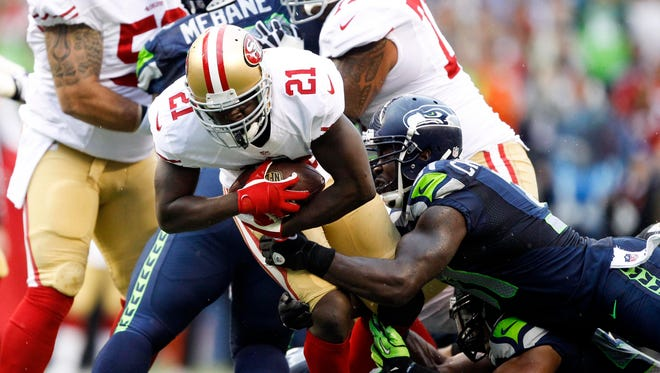 San Francisco 49ers running back Frank Gore (21) is tackled by Seattle Seahawks strong safety Kam Chancellor (31) and outside linebacker Malcolm Smith (53) during the first quarter at CenturyLink Field.
