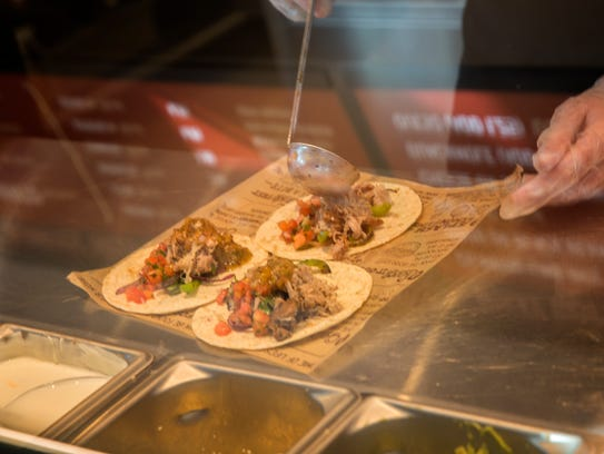 Danielle Moberg prepares tacos on Wednesday at Chipotle in Farmington.