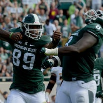 Michigan State defensive end Shilique Calhoun (89) and defensive lineman Lawrence Tjhomas (8) celebrate a sack of Central Michigan quarterback Cooper Rush (10) in the fourth quarter of the Spartans 30-10 win over the Chippewas at Spartan Stadium Sept. 26.