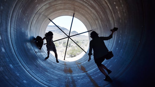 People walk through a Hyperloop tube after the first test of a propulsion system at the Hyperloop One Test and Safety site in North Las Vegas, Nevada.