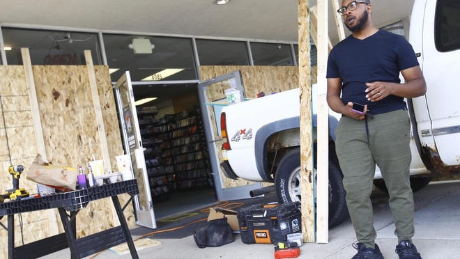 Darren King, assistant manager of Disc Replay at Forest Plaza on East State Street, works with other  employees on Thursday, June 4, 2020, to board up the store before a planned march against police brutality. Organizers say the walk will stop at the shopping center for a moment of silence. Looting occurred at businesses throughout Rockford after the first demonstration on Saturday.
