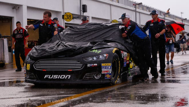 Crew members for Michael McDowell push the car into the garage area as heavy showers move into the area before the Coke Zero 400 at Daytona International Speedway.