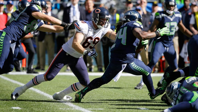 Seattle Seahawks running back Marshawn Lynch (24) runs the ball as Chicago Bears outside linebacker Jared Allen (69) reaches for a tackle attempt while being blocked by Seahawks' tight end Cooper Helfet, left, in the first half of an NFL football game, Sunday, Sept. 27, 2015, in Seattle.