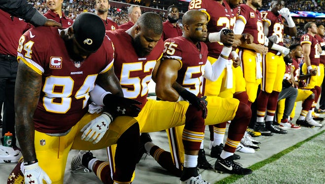 Washington Redskins tight end Niles Paul (84) and linebacker Ryan Anderson (52) and Washington Redskins linebacker Chris Carter (55) kneel with teammates during the playing of the national anthem before the game between the Washington Redskins and the Oakland Raiders at FedEx Field.