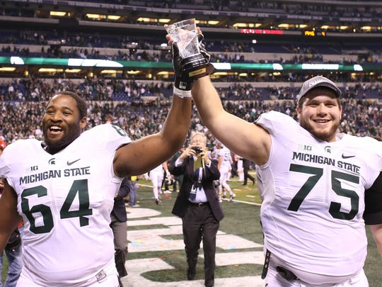 MSU offensive linemen Brandon Clemons (64) and Benny McGowan (75) hold up the Archie Griffin trophy for MVP after the game against the Iowa Hawkeyes in the Big Ten Conference football championship at Lucas Oil Stadium.