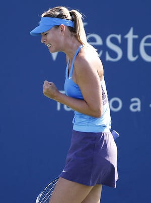 Maria Sharapova pumps her fist as she made a point Anastasia Pavlyuchenkova on the Grandstand during the Western and Southern Open. Sharapova went on to win, 6-4, 7-6 at the Lindner Family Tennis Center. Photo shot Thursday August 14, 2014.