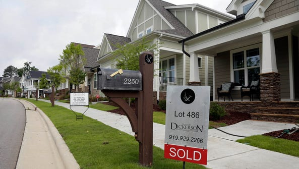 A sold sign is displayed in the yard of a home in the