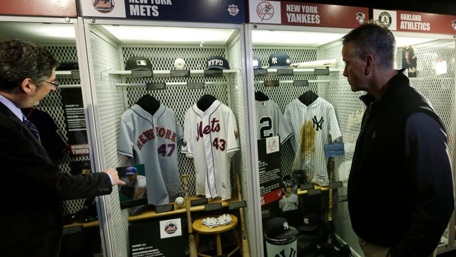 Former Atlanta and Mets pitcher Tom Glavine, right, looks at a Mets locker exhibit that displays his jersey and baseball from his 300th career win during his orientation visit at the Baseball Hall of Fame on Monday in Cooperstown. At left is Erik Strohl, vice president for exhibitions and collections at the hall.