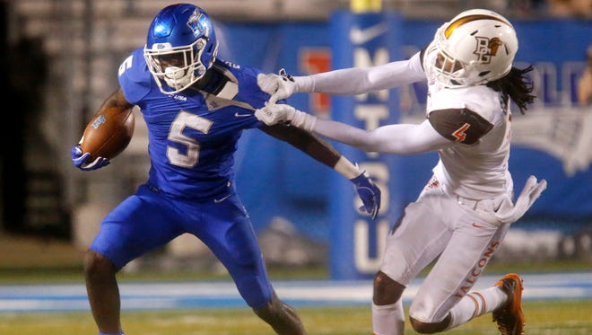 MTSU's Jocquez Bruce (5) runs the ball as Bowling Green's Fred Garth (4) tries to bring him down during the game, on Saturday, Sept. 23, 2017, at MTSU