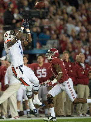 Auburn wide receiver D'haquille Williams (1) catches a pass as Alabama defensive back Eddie Jackson (4) guards him during the Iron Bowl at Bryant-Denny Stadium in Tuscaloosa, Ala., on Saturday, Nov. 29, 2014.