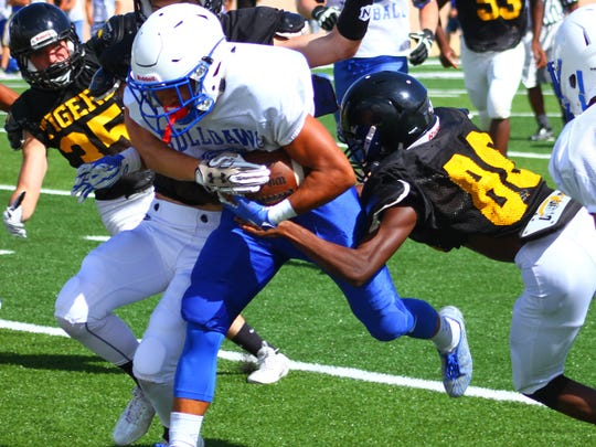A trio of Tigers try to bring down a Las Cruces player Friday afternoon.