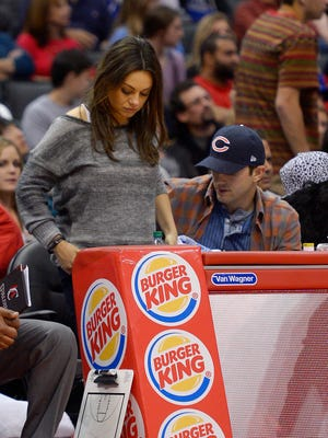 Mila Kunis, and Ashton Kutcher get up to leave after watching the Los Angeles Clippers play the Detroit Pistons on March 22 in Los Angeles.