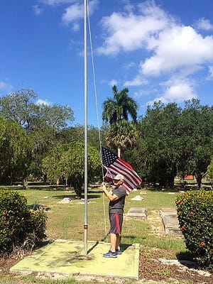 Charles David Hawkins raises an American flag on Sunday at the Oakridge section of the Fort Myers Cemetery. Hawkins is a veteran and says there was no flag flying when her arrived Sunday morning. On Saturday, several veterans raised a flag to honor the vetrans buried there.