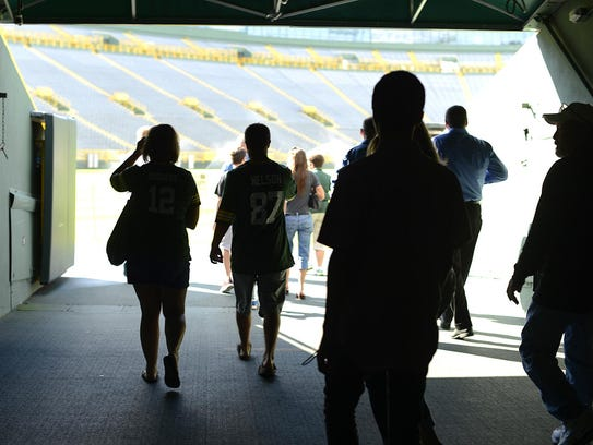 Fans walk through the players tunnel during a Lambeau