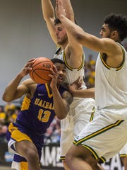 Albany's David Nichols, left, tries to find a hole in the UVM defense but instead finds Anthony Lamb, right, and Payton Henson during the America East Championship at Patrick Gym in March.