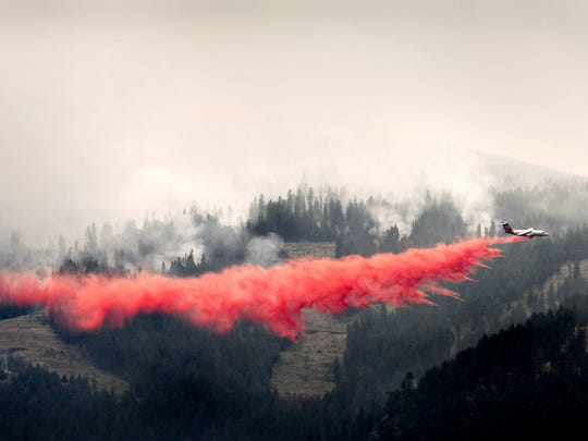 A bomber drops a load of fire retardant below the Lolo Peak fire creeping down the face of the ridge toward the Bitterroot Valley, Friday, Aug. 18, 2017 in Missoula, Mont. The Lolo Peak Fire in western Montana blew up overnight leading law enforcement officers to order the evacuation of up to 400 more homes west of the town of Lolo.