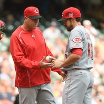 Cincinnati Reds manager Bryan Price relieves pitcher Sam LeCure (63) as catcher Brayan Pena (29) watches in the eighth inning during the game against the Milwaukee Brewers at Miller Park.