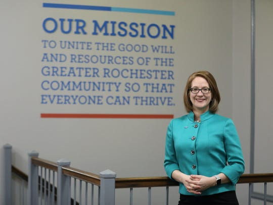 Jaime Saunders in front of the United Way of Greater Rochester's mission statement.