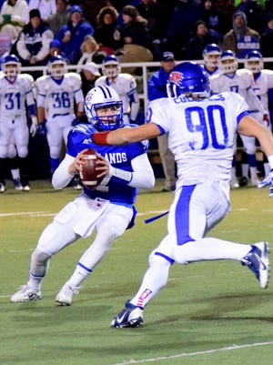 Highlands quarterback Beau Hoge looks to pass before tucking and headling to the end zone for a Bluebird touchdown as Covington Catholic's Jacob Steins defends.