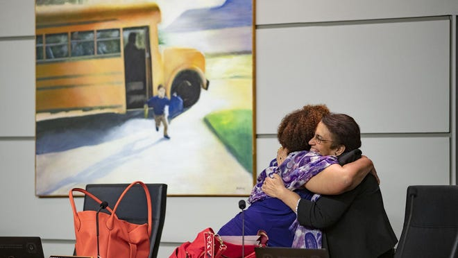 WEST PALM BEACH -- Dr. Alina Alonso, (right) Palm Beach County director of the Florida Department of Health, gives Dr. Debra Robinson, Palm Beach County School Board member, a hug before speaking to the School Board about the coronavirus on March 4.