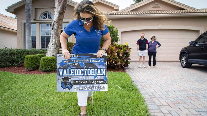 Wellington High School principal Cara Hayden plants a yard sign in valedictorian Max LeGates' yard as he looks on with his mom, Sheryl LeGates Monday in Lake Worth. Volunteers are placing graduation signs at the homes of all 626 members of the Wellington High School class of 2020 since there will be no live graduation ceremony this year due to the coronavirus outbreak. LeGates plans to attend the University of Florida.