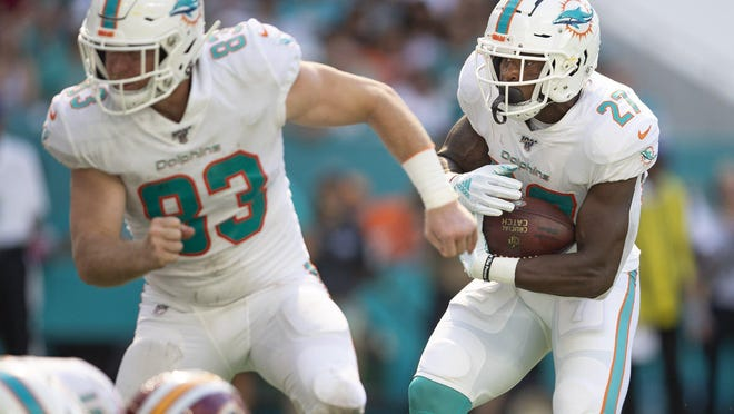 Miami Dolphins running back Kalen Ballage (27) follows the block of Miami Dolphins tight end Nick O'Leary (83) near the goal line during a game last season.