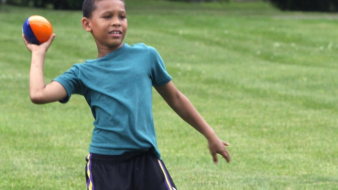 Samuel Simpson-Hardy gets ready to throw the football as he plays with friends at the Juneteenth celebration held Saturday at Junior's Place in Freeport.