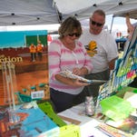 Pat and Joel Berger of Lehigh Acres shop for books at Maisy Barnette's booth selling Usborne books on Saturday, November 28, 2015 at Six Bends Harley Davidson during the Small Business Saturday event.