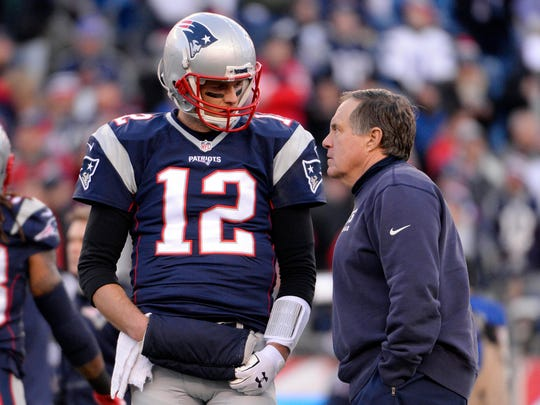 New England Patriots quarterback Tom Brady (12) talks with New England Patriots head coach Bill Belichick before the game against the Kansas City Chiefs in the AFC Divisional round playoff game at Gillette Stadium.