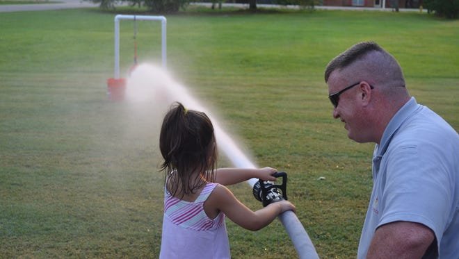 Fire Chief Matt Missildine demonstrates how tooperate a fire hose at one of last year's open house events.