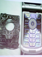 A photo of a burned component of a Motorola RAZR V3 next to a new model is projected on a screen during testimony in the Steven Avery trial in 2007.