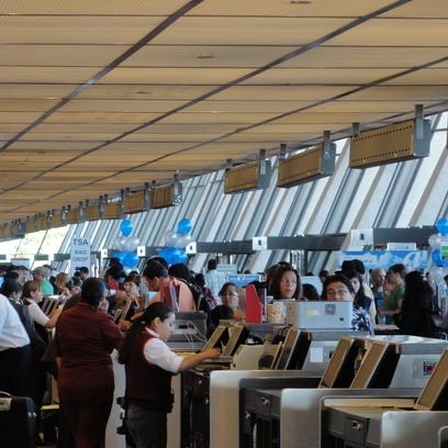 This file photo from August 2011 shows passengers line up at airline ticket counters at Washington Dulles International Airport.
