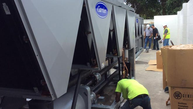 Workers install an outside chiller at Lewis Carroll Elementary on Merritt Island.