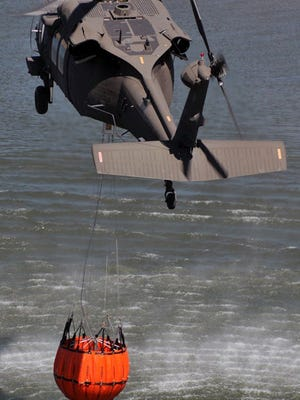 A file photo shows a Black Hawk helicopter with a water bucket for battling forest fires.