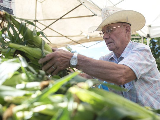 Roger Hebbert, from Bellvue, replenishes stacks of corn at the Fort Collins Farmers Market.