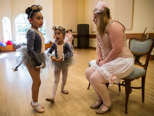 "Abigail Martinez, left, and Gigi Navarro, center, become excited as they talk to their dance instructor Simone Hoagboon, right, during Etudes de Ballet's ""Cinderella"" dress rehearsal at their dance studio on Wednesday, May 2, 2018."