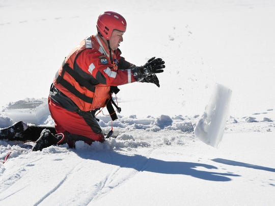 Henderson City Fire Department assistant chief Chad Moore throws a block of ice out of the way after cutting it with a chainsaw during an ice rescue training session at Audubon State Park Thursday.