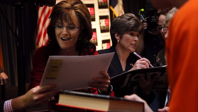 "Sarah Palin signs autographs beside Joni Ernst following the ShePAC ""Heels On, Gloves Off!"" rally to campaign for Joni Ernst, who is running for the U.S. Senate, at the West Des Moines Hy-Vee Conference Center on Sunday, April 27, 2014."